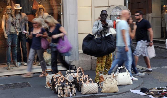 Un extracomunitario di colore vende borse contraffatte oggi in via del Corso a Roma. ANSA/CLAUDIO ONORATI/on